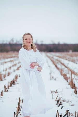 Barefoot woman in nightgown in winter field Foto de archivo