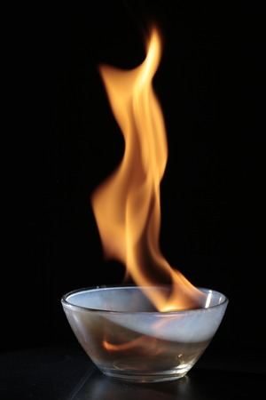 Small transparent glass with flames of fire