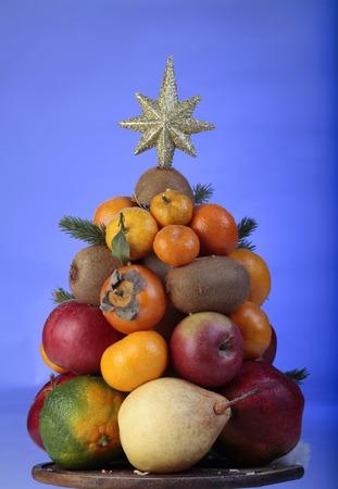 Fruit Christmas tree on table on blue background. 版權商用圖片