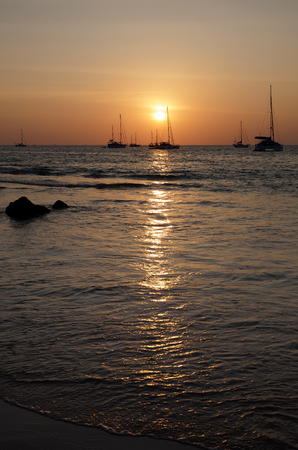 Sunset on the sea with a sailboats.