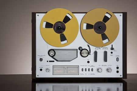 Vintage Reel-to-Reel stereo tape deck recorder closeup on the dark background