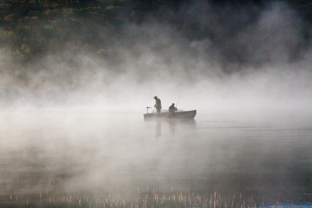 resting rod fishing: Fishermen in the foggy lake