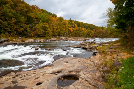 Autumn forest rocks river in the woods with yellow trees foliage photo