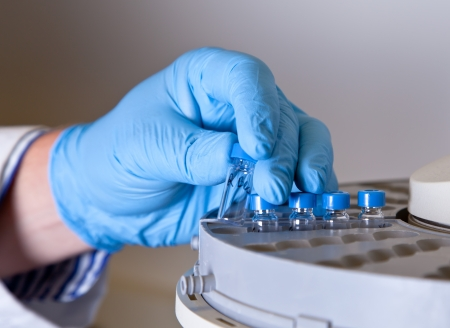 chromatograph: Scientist holds a chemical sample bottle