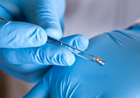 laboratory labware: Scientist holds standard weight with tweezers Stock Photo