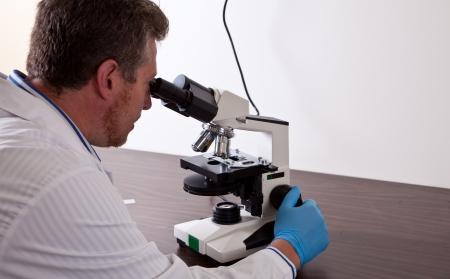 Lab wetenschapper kijkt naar microscoop
