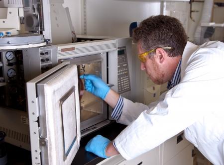 Scientist prepares chromatograph oven installing column photo