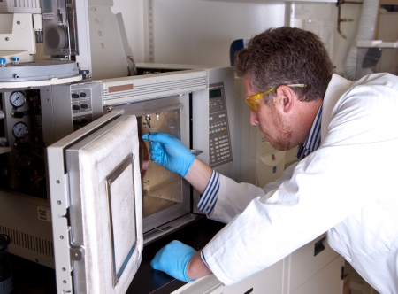 Scientist prepares chromatograph oven installing column