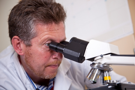 Scientist works with microscope photo