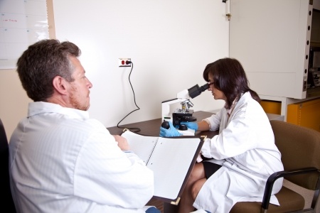 Scientists coworkers near by microscope photo