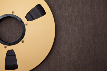 masters of rock: Professional audio metal reel on brown background  Stock Photo