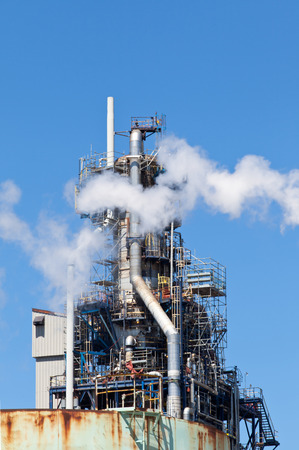 refined: Refined Petroleum Petrochemical Plant Smokestack Pipeline with blue sky Stock Photo