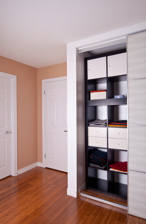 closet door: Built-in closet with sliding door shelving storage organization solution filled with clothes