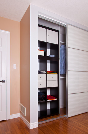 Delicieux Built In Closet With Sliding Door Shelving Storage Organization Solution  Filled With Clothes Stock Photo
