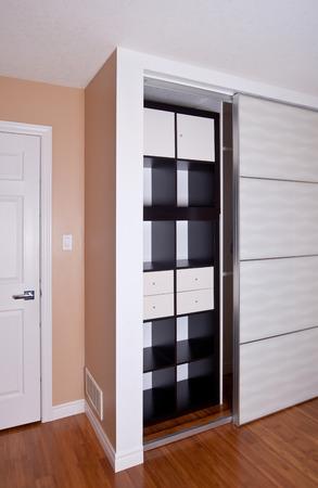 view an elegant wardrobe: Built-in closet with sliding door shelving storage organization solution, empty shelves