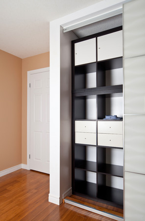 view of a comfortable bedroom: Built-in closet with sliding door shelving storage organization solution, empty shelves