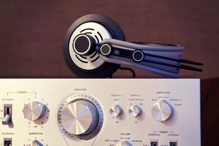 Audio Stereo Headphones on the top of Vintage Amplifier Front View Imagens