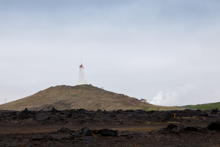 Iceland lighthouse Reykjanesviti with rocky volcanic soil and gray sky landscape