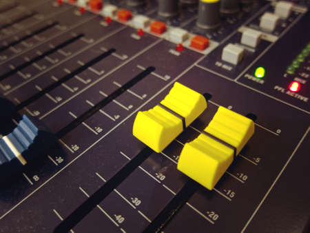 Audio mixing console board channel yellow knobs and buttons closeup
