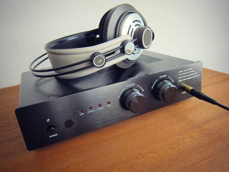 Schwarzer DAC Kopfhörerverstärker mit angeschlossenem Kopfhörer auf dem Holztisch Standard-Bild