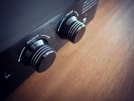 Stereo Audio Amplifier Source knob, black device on the wooden desk