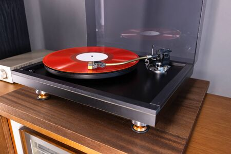 Vintage Stereo Turntable Plays Red Vinyl Record Album, angled view