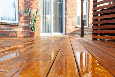 Backyard wooden deck floor boards with fresh brown stain, angled view
