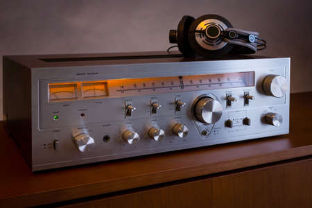 Vintage Audio Stereo Receiver with shiny metal front panel with headphones