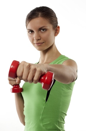 sports form: The girl with dumbbells in the hands, dressed in the sports form, costs on a white background. The hand from dumbbells is extended before itself.