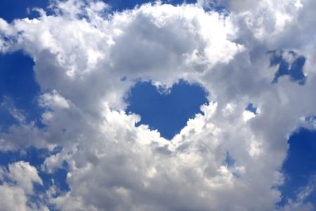 青空にふわふわの雲を灰色。ハートの形で雲ブレークの中心 写真素材