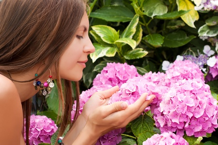 Beautiful young woman smelling purple flowers in a garden