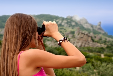 Young woman watching through binoculars in the mountains