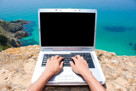 laptop keyboard: Person using laptop at beautiful location by the sea Stock Photo