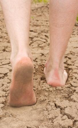 Man geht auf dem Ton rissige Erde. Beine Nahaufnahme. Lizenzfreie Bilder
