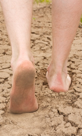 Man goes on the clay cracked earth. Legs closeup.
