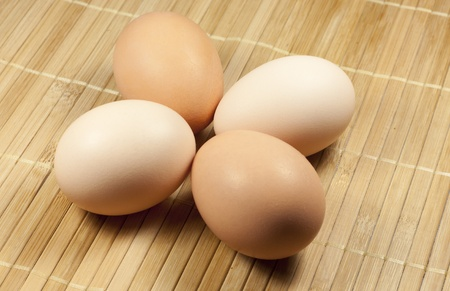 two beige and two brown eggs are on a striped rug photo