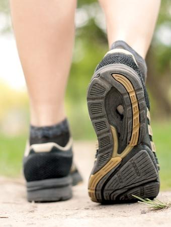 フォレストでは、スポーツの靴のクローズ アップのトレイルをハイキングを歩いて女性