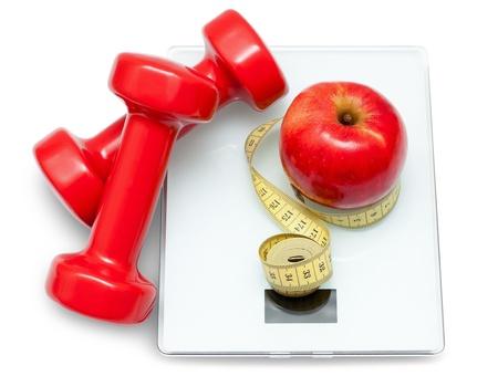 Scales, Hanteln, rotem Apfel und Maßband auf dem weißen Hintergrund. Diät-Konzept.