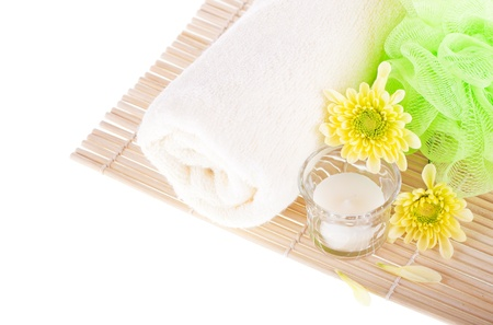 Towel, flowers, candle and bamboo mat on white background  Spa concept