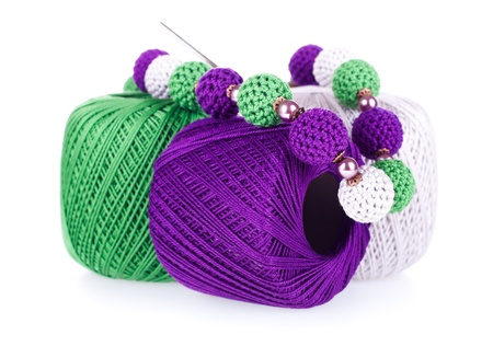Three colored balls of cotton knitting yarn with crochet and knitted necklace on the white background photo