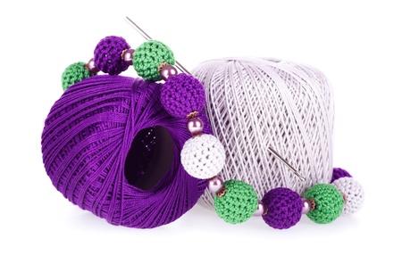gomitoli di lana: Due palle colorate di cotone filato per maglieria, con uncinetto e maglia collana sullo sfondo bianco Archivio Fotografico