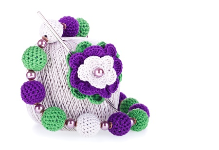 bead embroidery: Grey ball of cotton knitting yarn with crochet, knitted flower and necklace on the white background Stock Photo