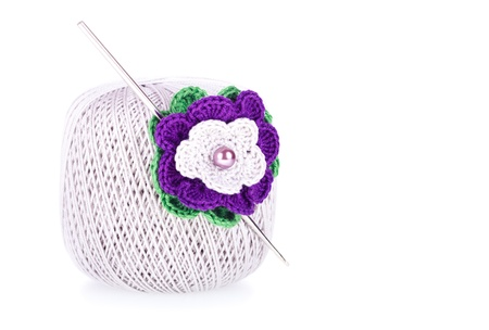 Grey ball of cotton knitting yarn with crochet and knitted flower on the white background photo