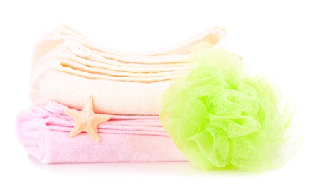Two towels beige and pink, bath sponge and starfish on the white background photo