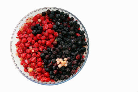 frozen berries in the shape of a circle with the symbol of yin and yang, female and male. Berries in a round glass shape on a light background. Top view, there is a free space for advertising.