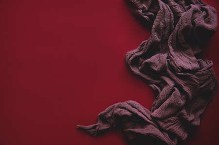 On a red background-a red textured fabric. Stylized photo for advertising and presentation. in an artistic style, elegant lines emphasize individuality and exclusivity.