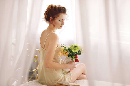 Beautiful young woman in a nightgown. morning dreams of a girl in love. The bouquet in your hands reminds you of your beloved man. a room for a girl. playful mood. about love