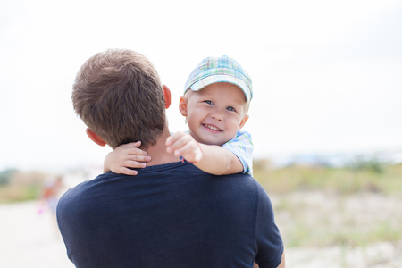he laughs: Happy little boy on his fathers hands, hugs, smiles, laughs,