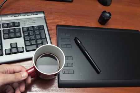 De grafiekentablet met een potlood, een deel van het notitieboekje en de kop van koffie op een zwarte houten lijst, sluiten omhoog. Grafische tablet, toetsenbord, tafel, koffie, pen.