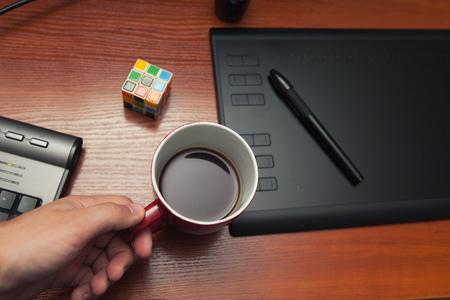 Break, rust tijdens het werkproces, een kopje koffie, een kubus van rubik, een puzzel. Grafisch tablet op een houten tafel.